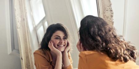 o femeie zâmbind în oglinda